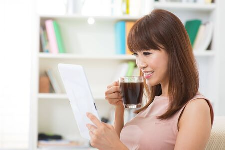 Asian female enjoying cup of coffee and digital tablet inside house photo