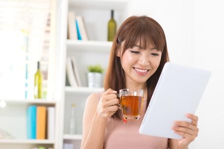 bookshelf digital: Asian female enjoying cup of tea looking at digital tablet computer inside house