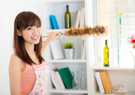 Happy housewife cleaning house with duster Stock Photo