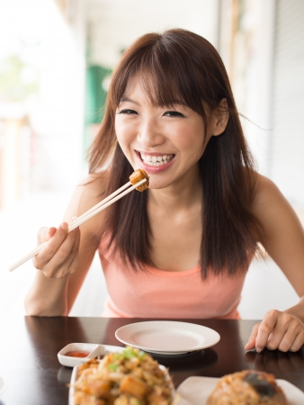Young Asian woman enjoying meal at restaurant photo