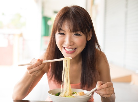 chinese noodles: Portrait of happy smiling young Asian woman eating Asian noodles Stock Photo