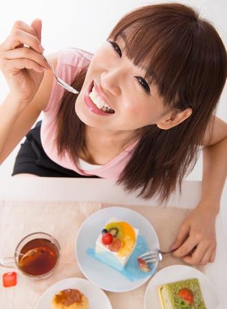 Fun Asian woman eating the cake inside house photo