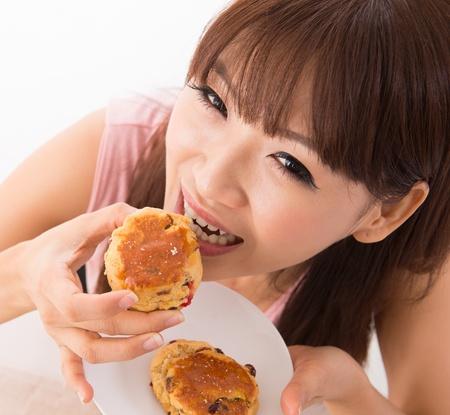 woman eating cake: Young Asian woman enjoying scones