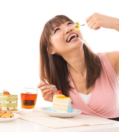 Lächelnde asiatische Frau essen Kuchen im Wohnzimmer in ihrem Haus