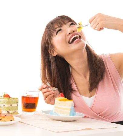 unhealthy living: Smiling Asian woman eating cakes in the living room in her house