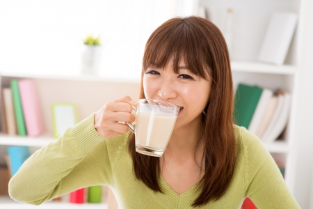 soy: Young Asian woman drinking a glass of soy milk at home Stock Photo