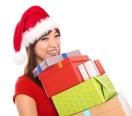 santa cap: Smiling Asian Christmas woman holding gifts wearing Santa hat, isolated on white background.
