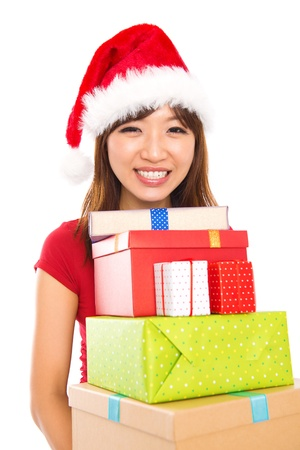 Beautiful Christmas shopping woman holding many Christmas gifts in her arms wearing santa hat, isolated on white background. photo