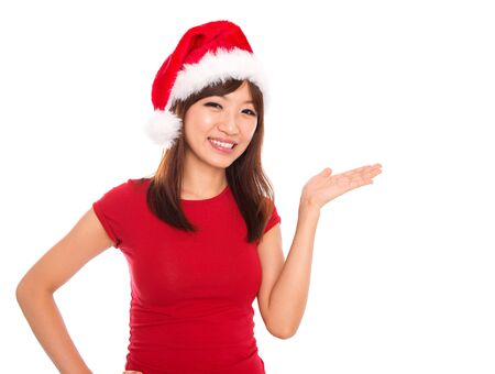 Asian Christmas woman presenting  showing copy space standing in Santa hat. Isolated on white background smiling looking at camera. photo