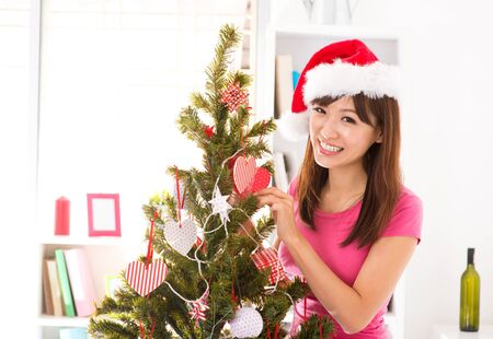 Beautiful Asian woman decorating Christmas tree in her house photo