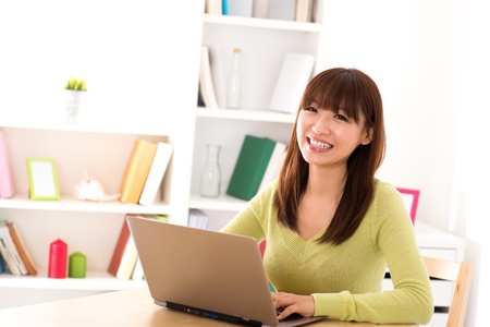 Happy Asian girl using laptop computer for online shopping at home photo