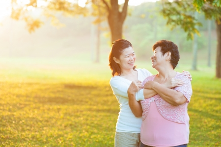 candid: Happy Asian senior mother with her daughter at outdoor park