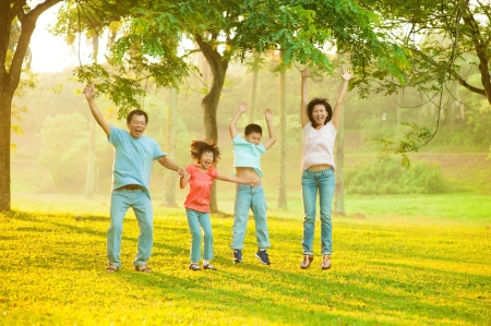 Joyful Asian family jumping together in the park photo