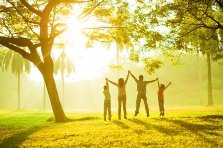 즐거운 아시아 가족의 후면보기 공원에서 함께 점프