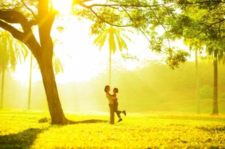 padres hablando con hijos: Asia madre abrazando a su hija en el parque al aire libre Foto de archivo