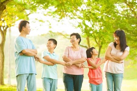familias unidas: Tres generaciones de la familia asiática de la mano en el parque al aire libre Foto de archivo