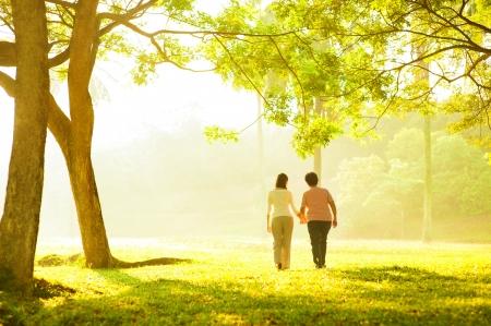 senioren wandelen: Aziatische senior moeder en volwassen dochter hand in hand lopen in openlucht park Stockfoto