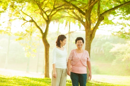 Asian senior mother and adult daughter walking at outdoor green park photo
