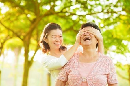 Hija adulta asiática que cubre sus ojos de la madre de alto nivel con las manos en el parque al aire libre Foto de archivo