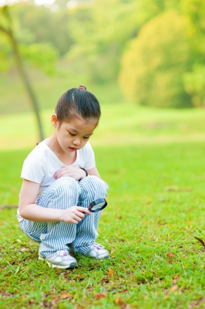 Little Asian girl exploring nature by magnifier photo
