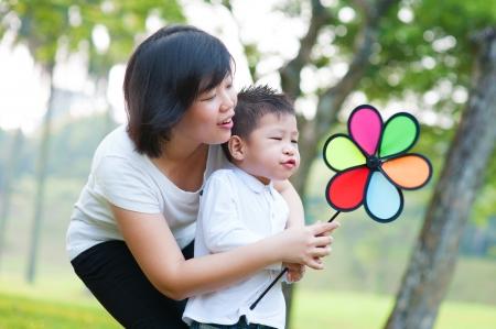 ni�os jugando en el parque: Asia madre e hijo que juegan en el parque al aire libre molino de viento Foto de archivo