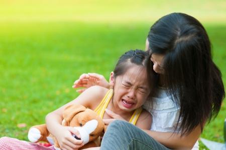 niño llorando: Madre consolando a su hija llorando