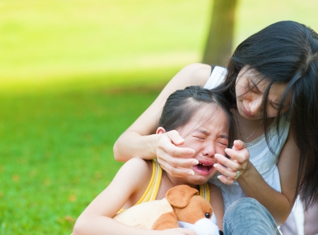 child crying: Asian mother is comforting her crying daughter Stock Photo