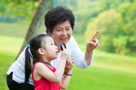 Asian grandmother and granddaughter exploring nature by magnifier photo