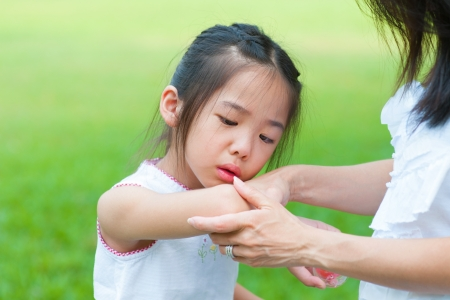 Mother checking wound to her daughter at outdoor park photo