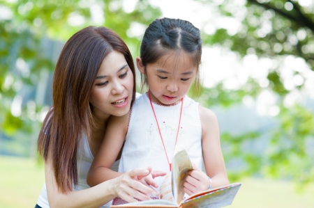 two parents: Beautiful little girl reading book with her mother and smiling. Summer park in background. Stock Photo