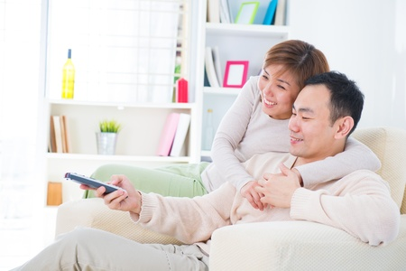 Portrait of happy Asian couple sitting on couch and watching television together photo