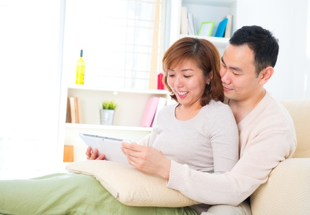 Beautiful Asian couple with digital tablet computer. Sitting on couch. photo