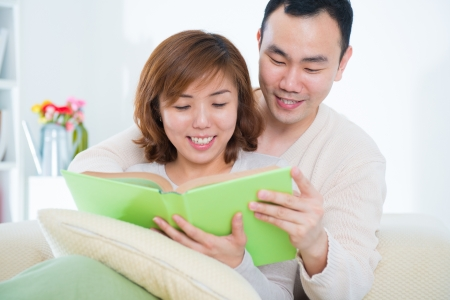 Beautiful loving Asian couple reading a book on the sofa photo