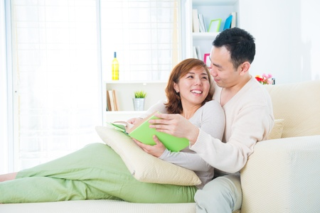 Asian couple enjoying their reading on sofa, indoor home photo