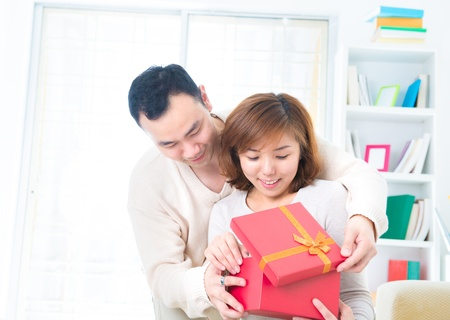 open present: Asian man surprises his girlfriend with a gift