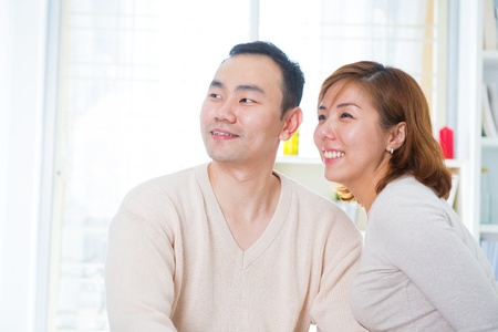 Smiling Asian couple looking away, indoor home photo