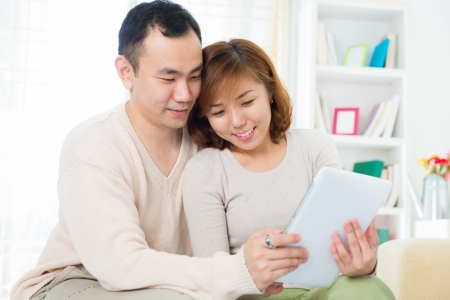 Asian couple using digital tablet computer at home photo