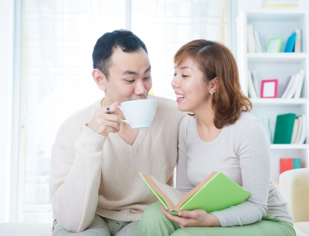 Asian couple reading booking and drinking tea/coffee at home photo