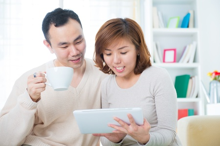 Asian couple drinking tea  coffee and using tablet computer at home photo