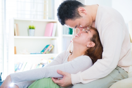 Loving Asian couple having fun time at home photo