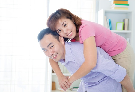 Portrait of a young Asian man giving piggyback to woman indoor. photo