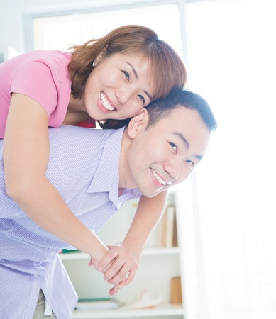 Asian couple piggyback ride indoor photo