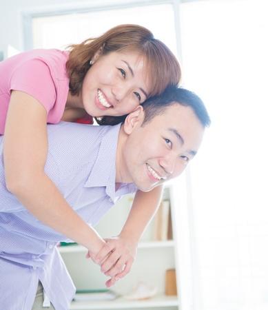 Asian couple piggyback ride indoor