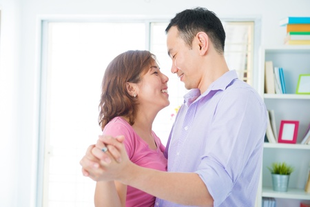 Fun Asian couple dancing at home photo
