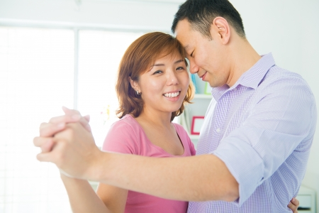 Romantic Asian young couple dancing at home photo