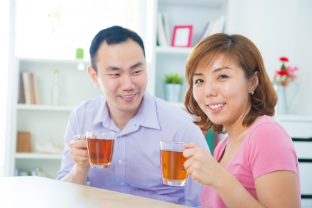 Attractive asian couple enjoying tea/coffee at home photo