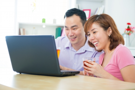 Asian couple using notebook and drinking tea  coffee at home photo
