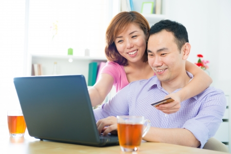 Happy Asian couple shopping online with credit card and computer at home photo