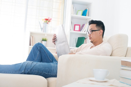 Southeast Asian male reading news paper at home, indoor lifestyle photo