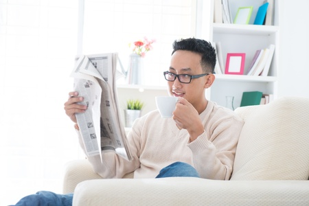 Southeast Asian male drinking coffee while reading news paper sitting on sofa at home, indoor lifestyle photo